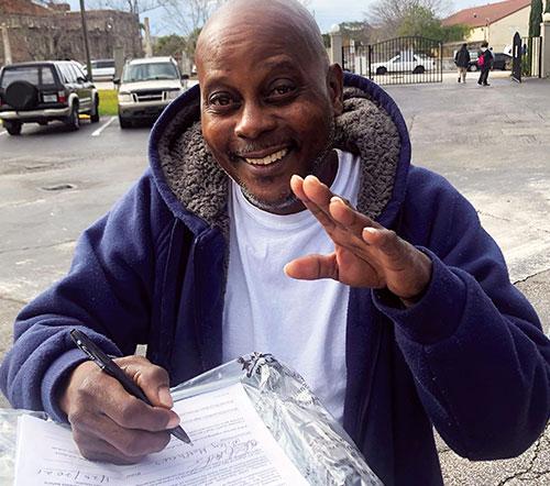 Un hombre negro está sonriendo y saludando a la cámara mientras llena su papeleo de elegibilidad.