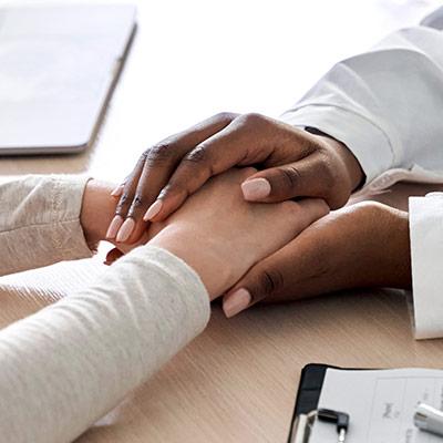 Imagen de las manos de una persona negra sosteniendo las manos de una persona blanca desde el otro lado de la mesa.