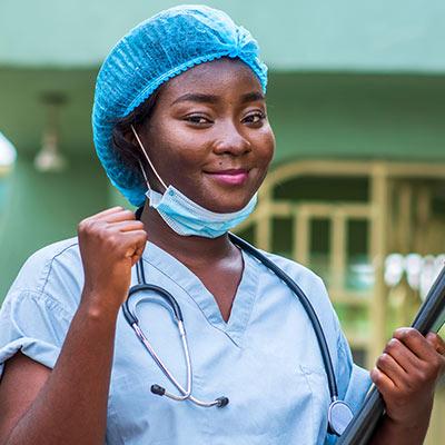 """Una doctora negra lleva una redecilla quirúrgica y la máscara le llega hasta la barbilla. Ella luce triunfante levantando su puño en forma de celebración como si dijera: """"¡Lo hicimos!"""" Lleva un estetoscopio alrededor del cuello y sostiene un folio negro."""