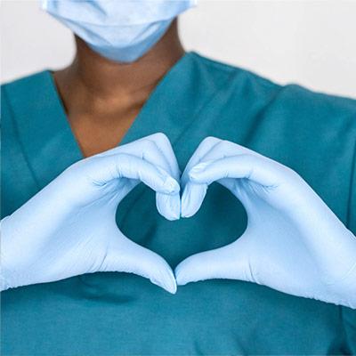 Manos enguantadas haciendo un símbolo de corazón. La persona lleva batas de color verde azulado y una máscara azul y guantes quirúrgicos.