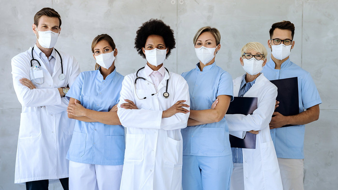 A multicultural, multi racial, multi gender group photo of doctors and nurses. They are all masked. Two of the doctors are wearing stethoscopes. And a nurse and the third doctor are holding clipboards. There are six people in total, arranged in a backwards v shape.