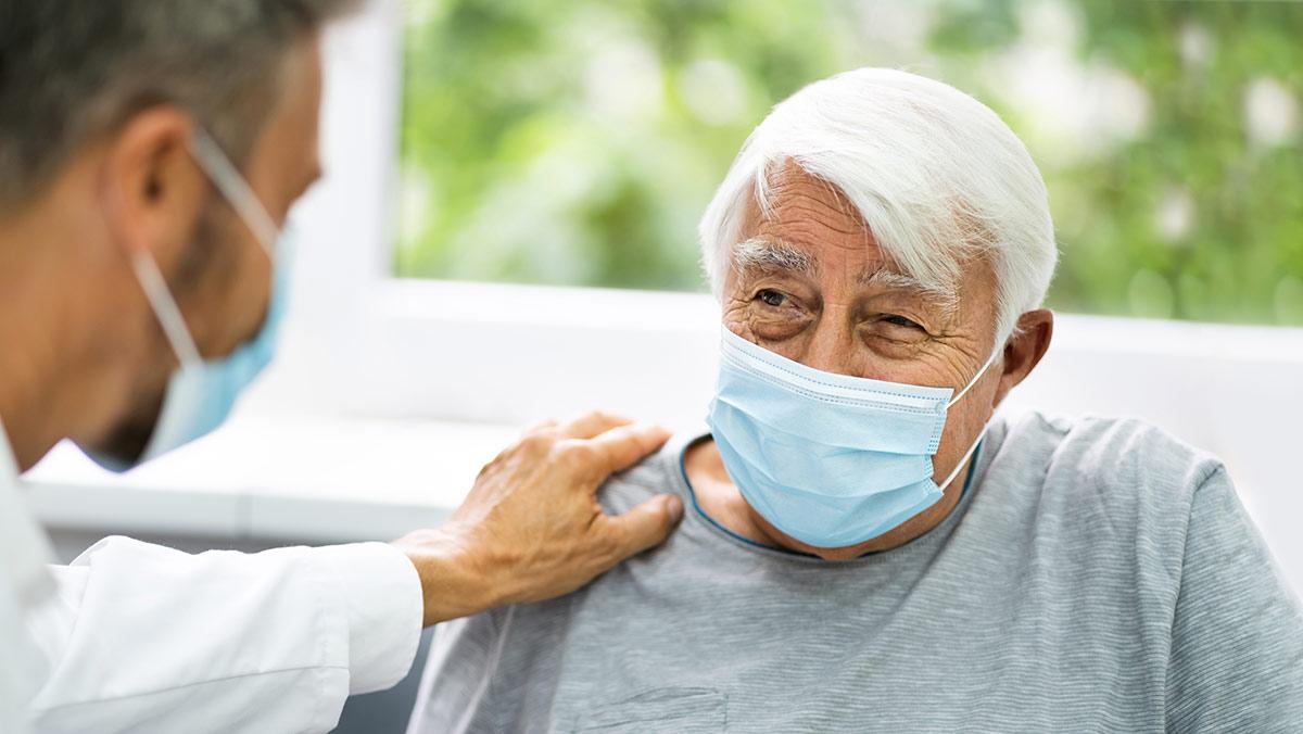 Imagen de un anciano blanco que es un paciente. Un médico tiene su mano sobre su hombro para tranquilizarlo. El paciente parece estar sonriendo.