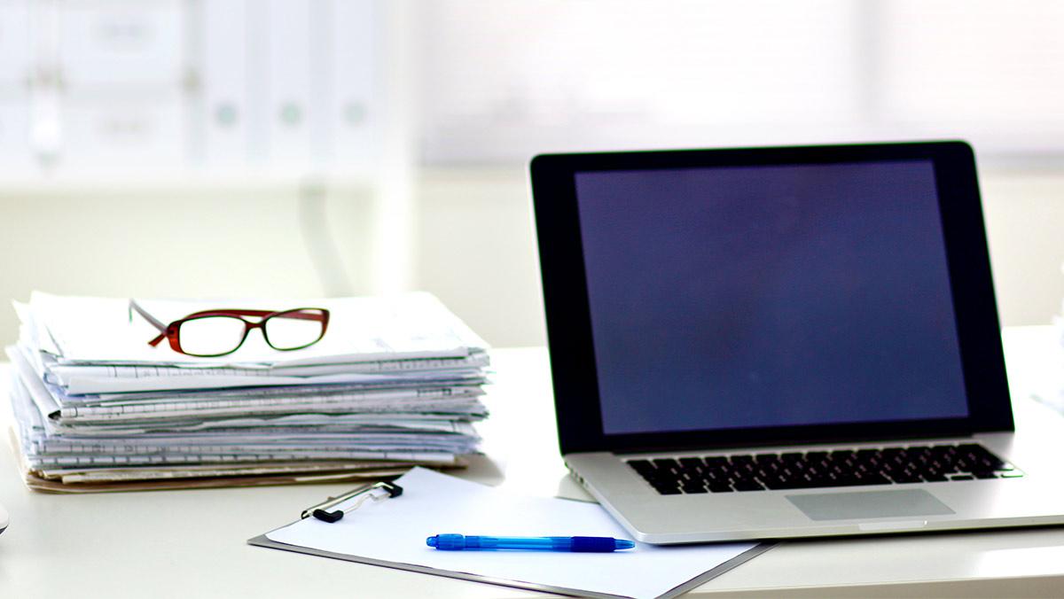 A la derecha hay una computadora portátil de Apple sobre una mesa. Debajo de la computadora portátil ya la izquierda hay un portapapeles con un bolígrafo. Detrás del portapapeles hay una pila de informes y gráficos con un par de anteojos de lectura encima.
