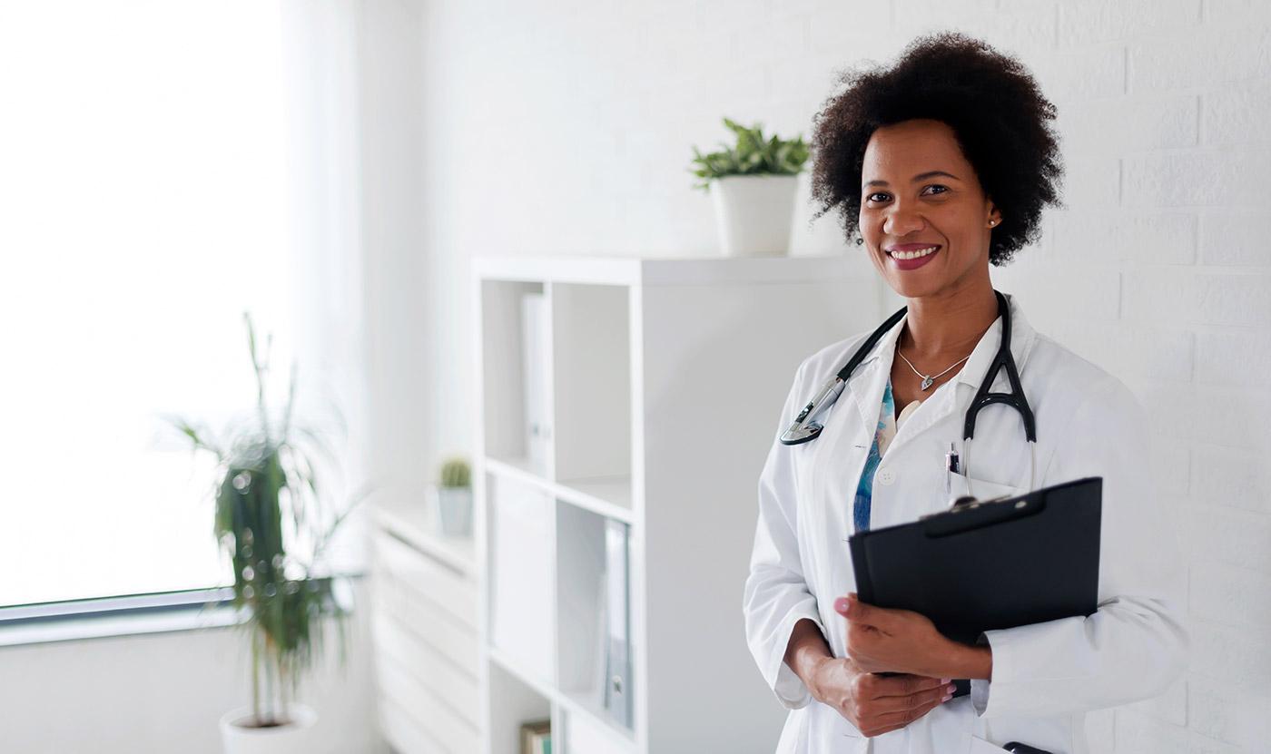 Imagen de una doctora negra. Ella sostiene un portapapeles negro y está de pie en una oficina de color blanco brillante con algunas plantas en macetas en el fondo.
